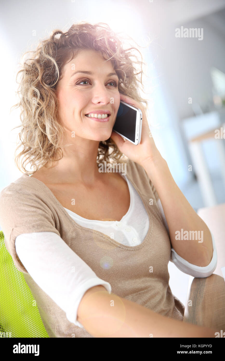 Smiling woman talking on the phone - Stock Image