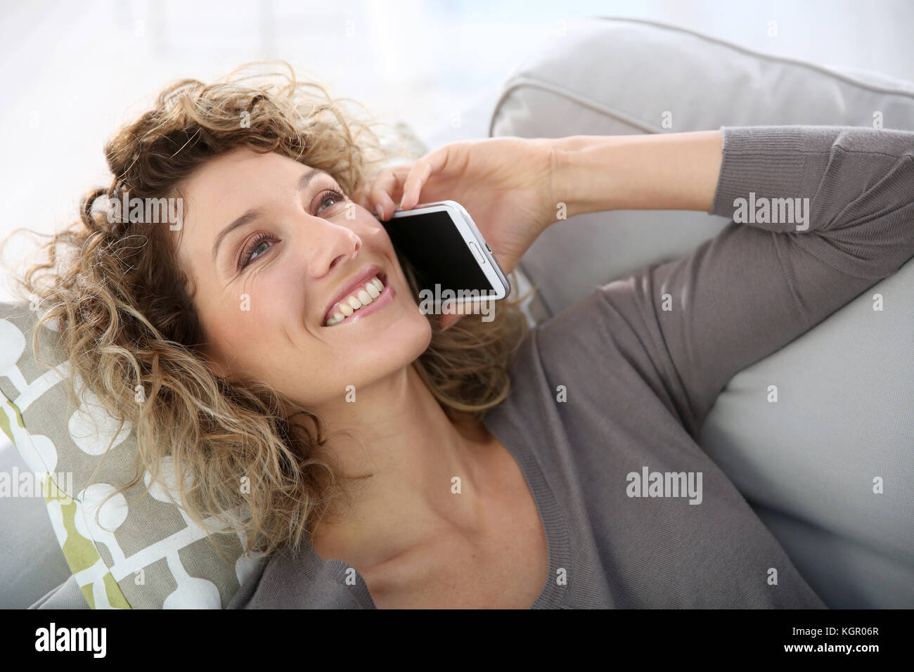 Woman talking on smartphone laid in sofa Stock Photo