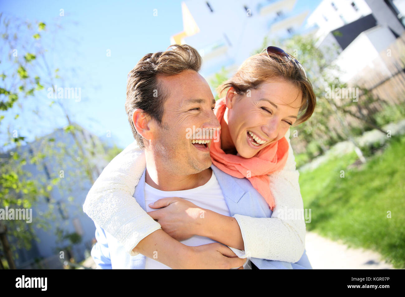 Man giving piggyback ride to woman in town - Stock Image