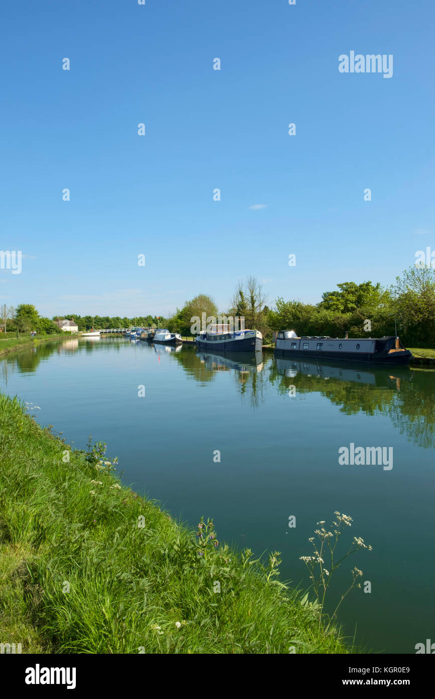 Boat moorings and people walking the towpath of the tranquil Gloucester & Sharpness Canal at Purton in summer - Stock Image