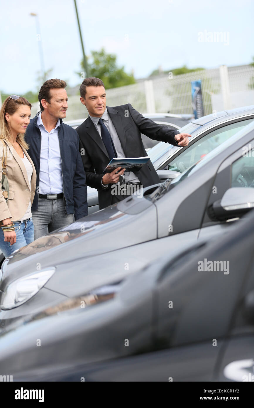 Car dealer showing vehicles to couple - Stock Image