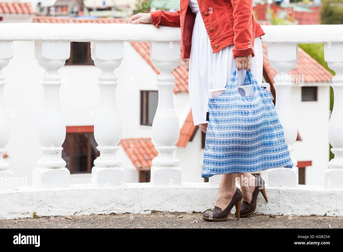 Woman carrying groceries in a reusable shopping bag - Stock Image