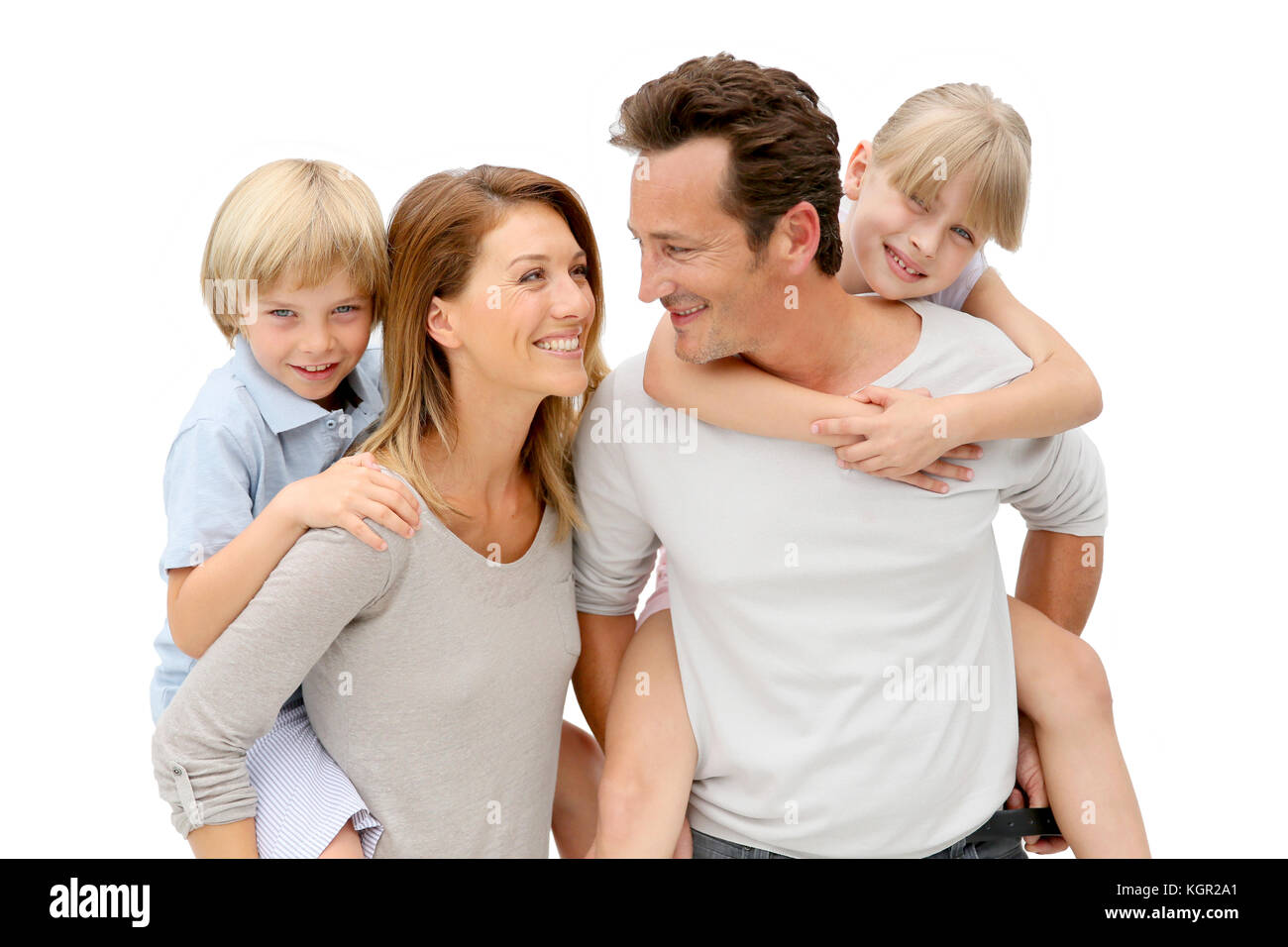 Parents giving piggyback ride to kids - Stock Image