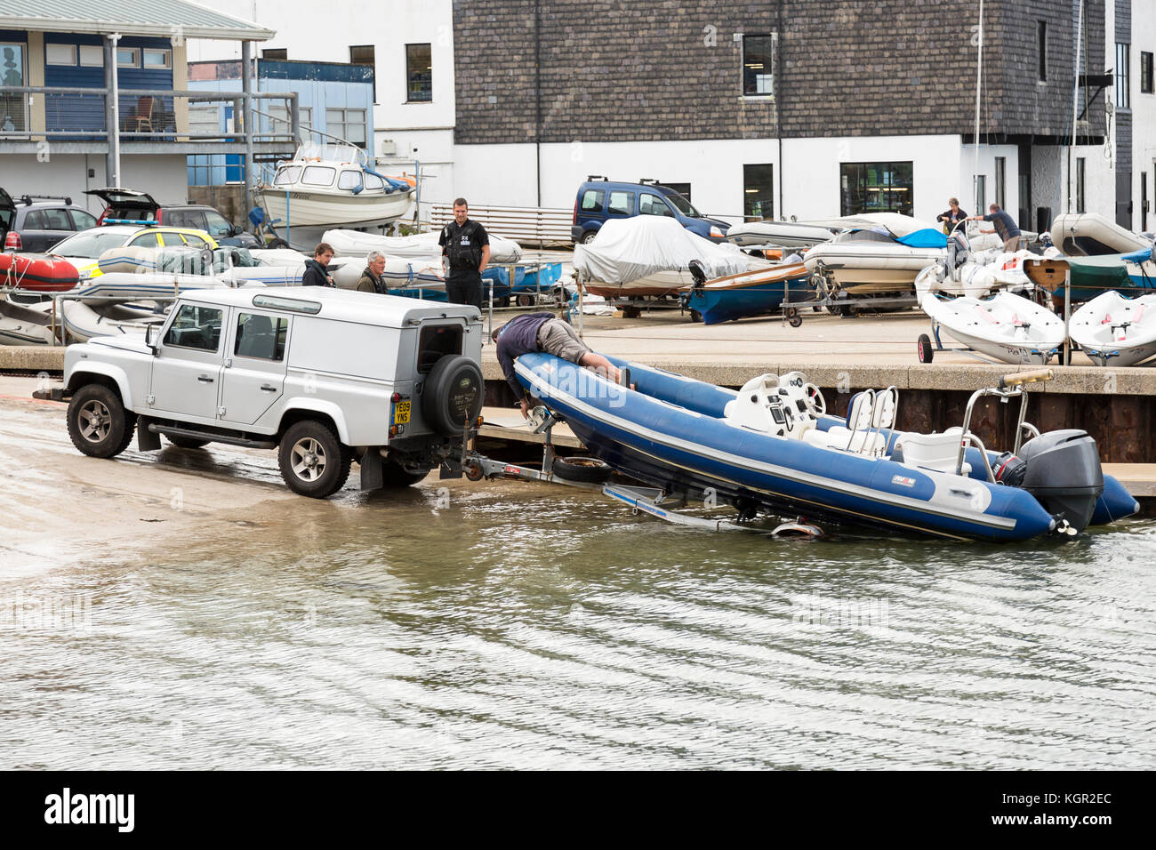 launching rigid inflatable boat off Falmouth harbour slipway, man hangs over bow to release winch while onlookers - Stock Image
