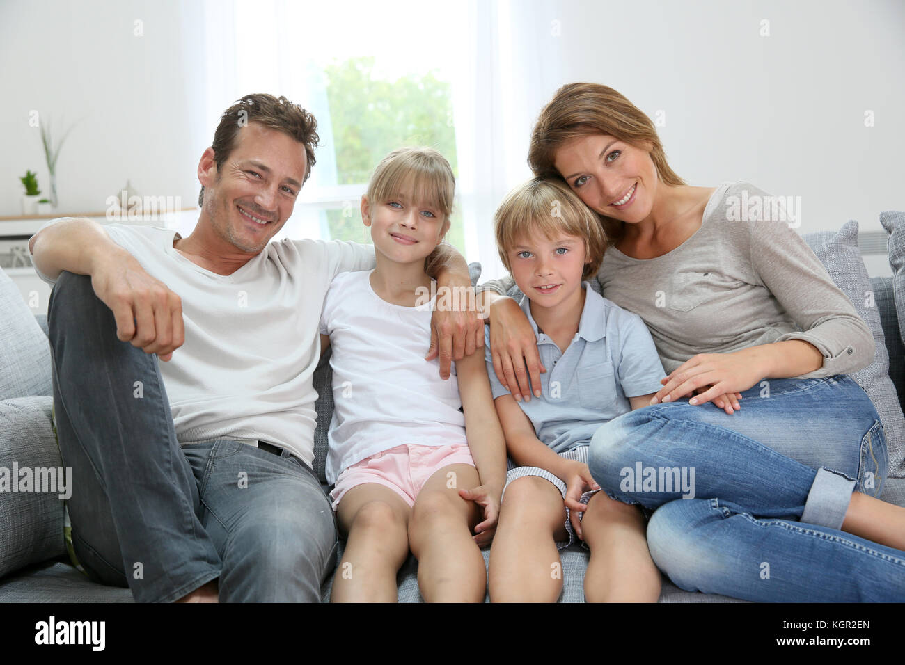 Happy family relaxing on couch at home Stock Photo