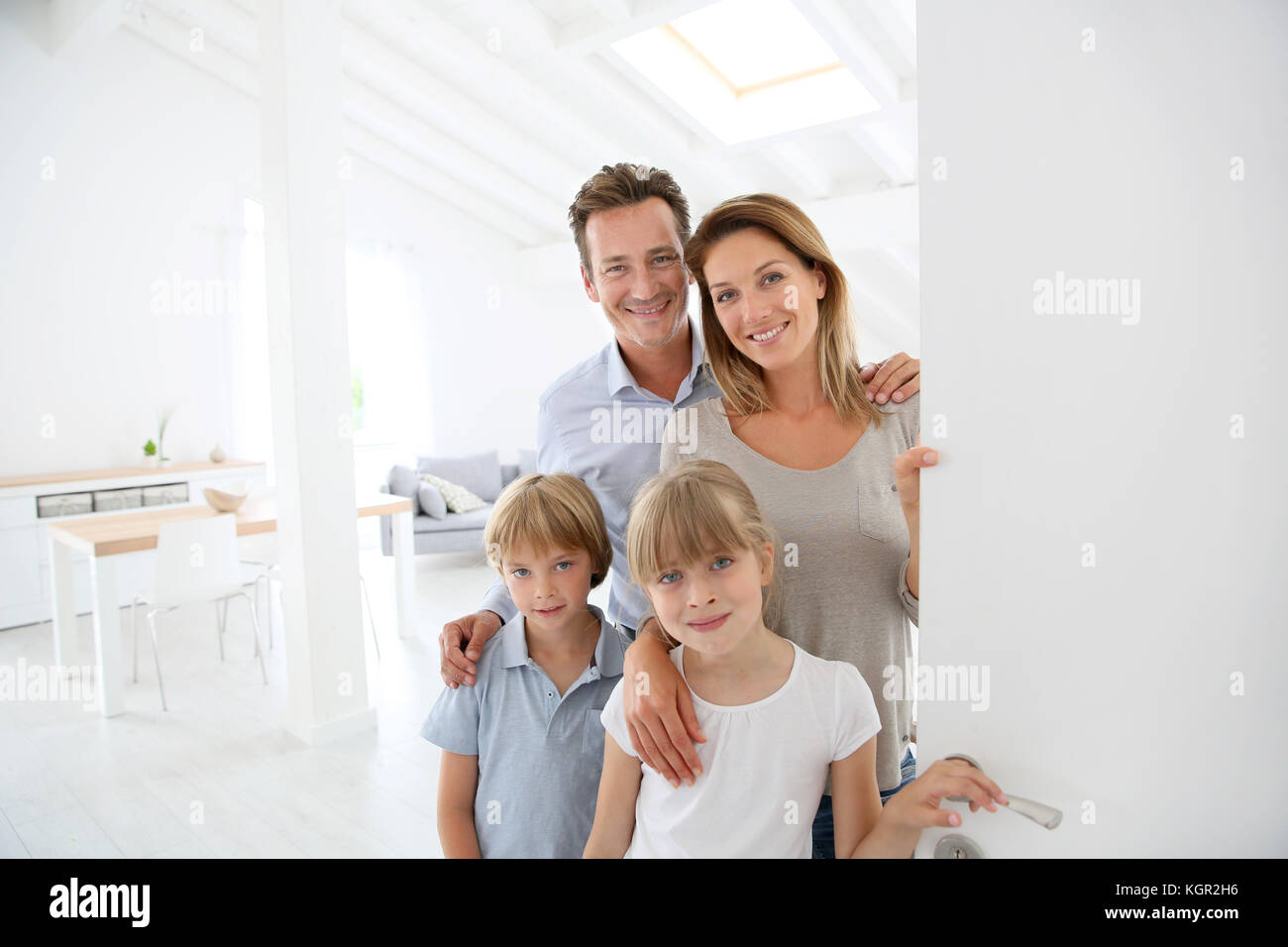Family welcoming people at entrance door - Stock Image