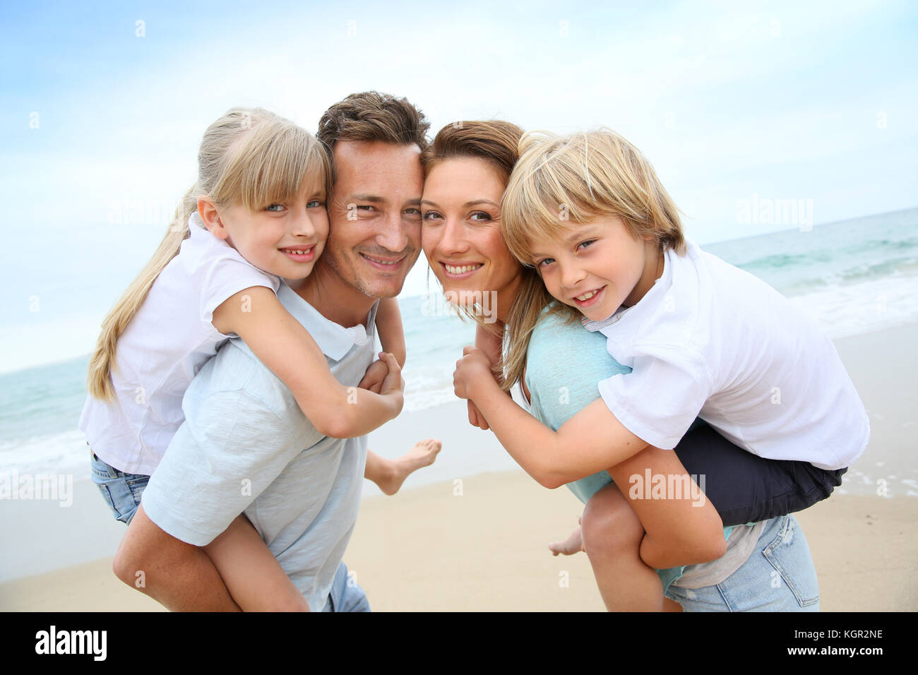 Parents giving piggyback ride to kids at the beach - Stock Image