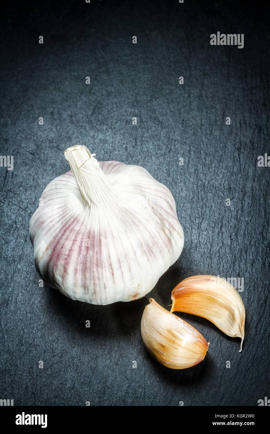 Garlic bulb and cloves (Allium sativum) on a black slate surface. Stock Photo