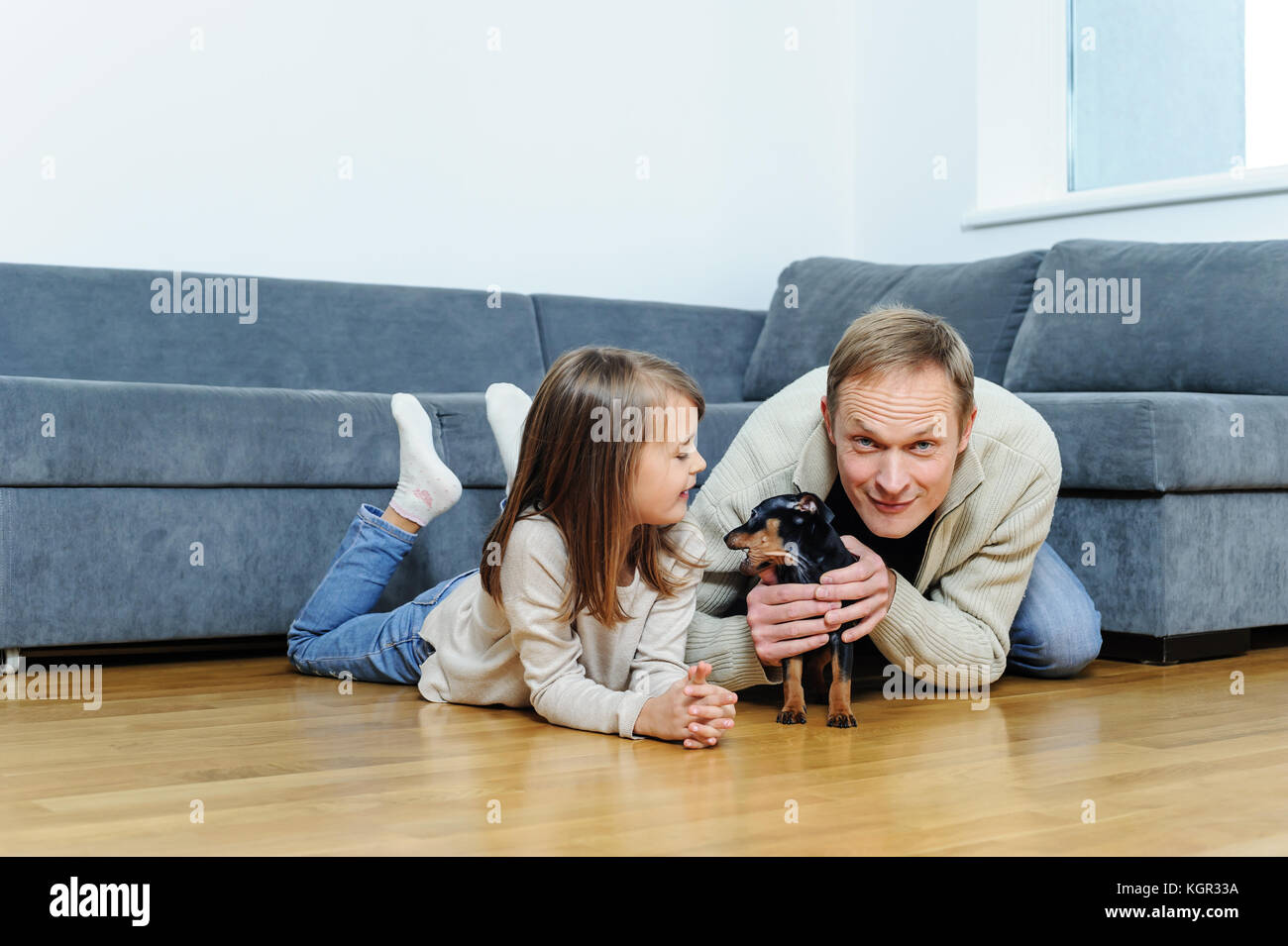 The girl and the man with the puppy are on the floor in the room. - Stock Image