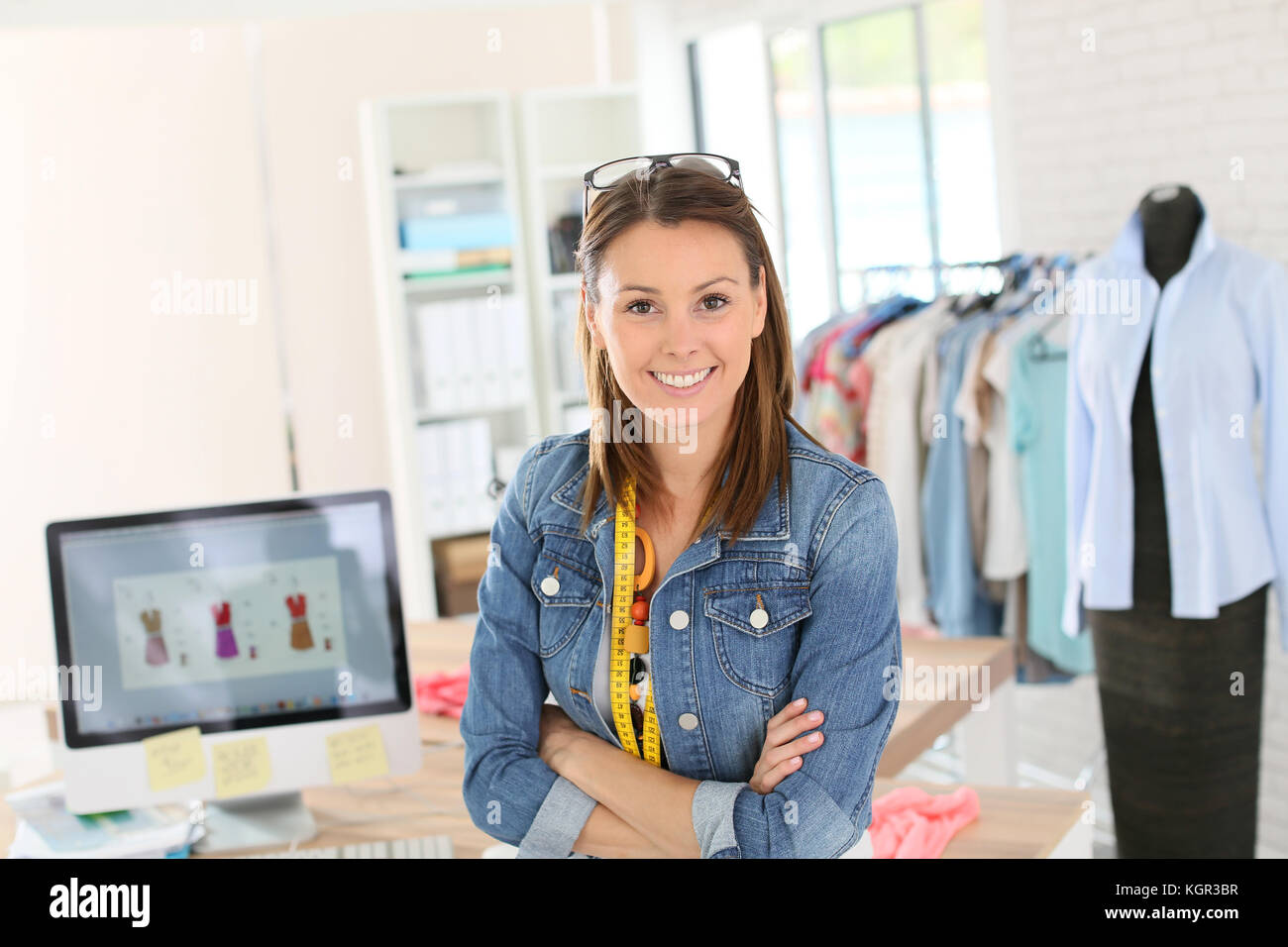 Portrait of smiling fashion designer in studio - Stock Image