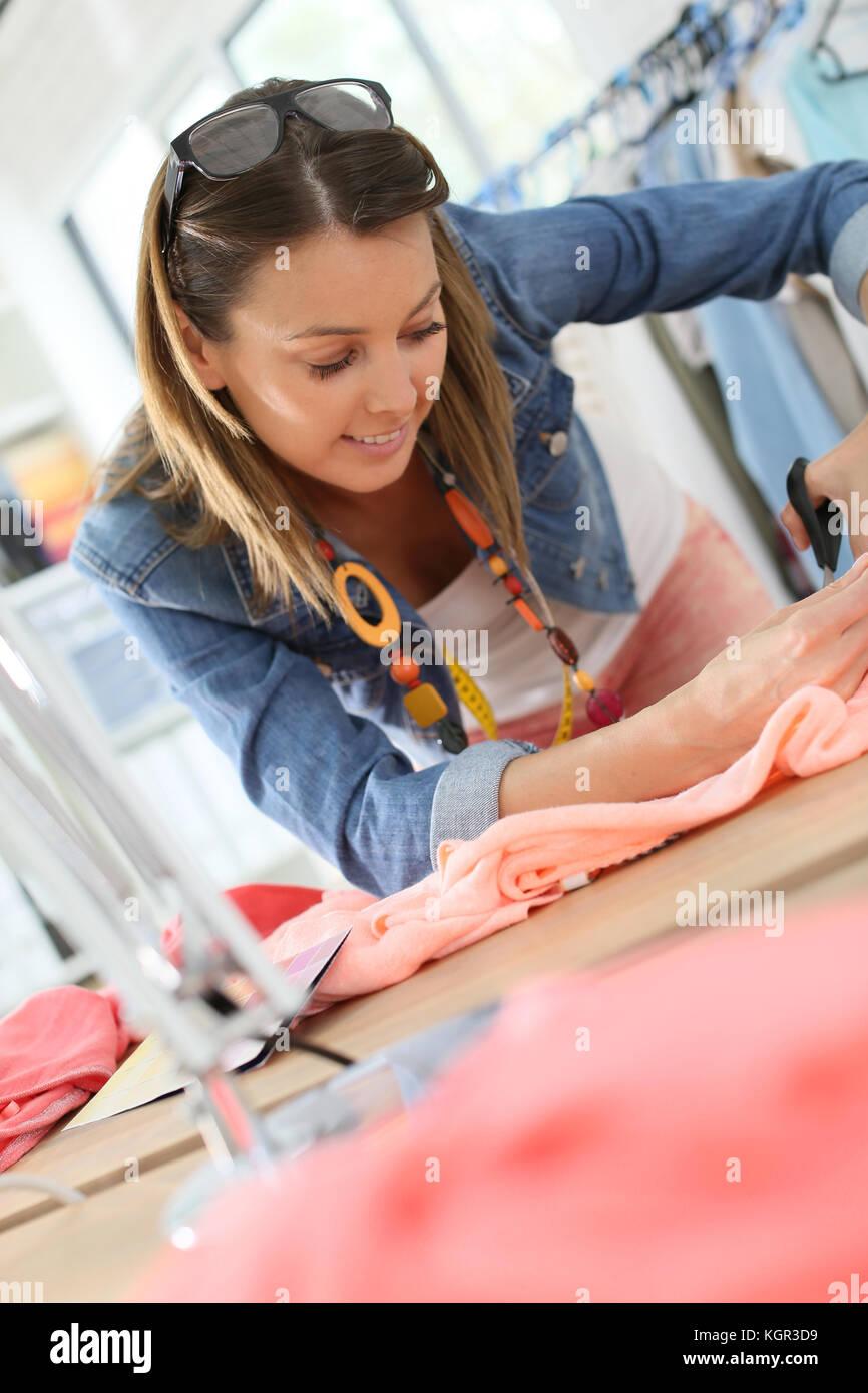 Fashion designer cutting fabric on dressmaking table - Stock Image