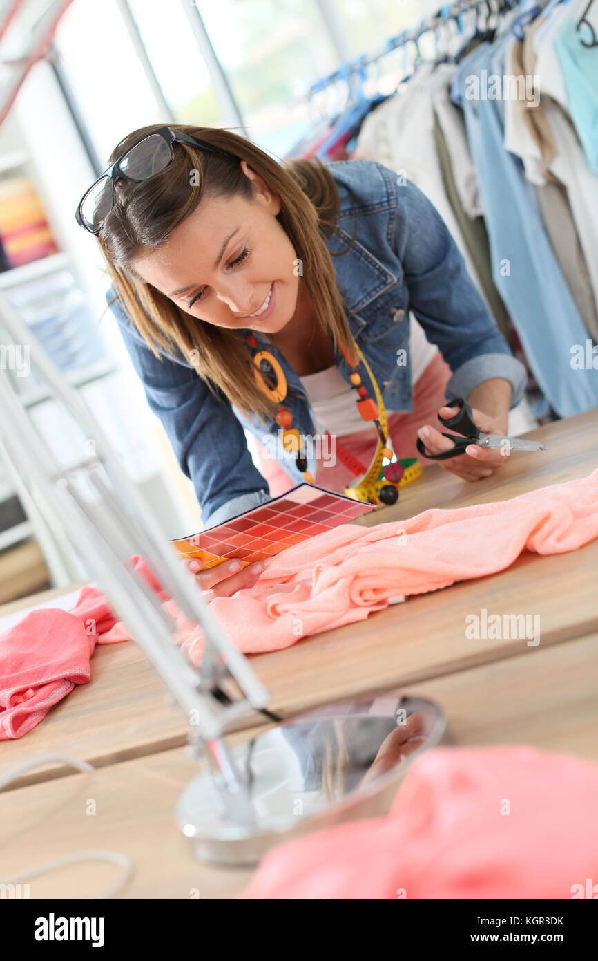 Fashion designer cutting fabric on dressmaking table - Stock Image