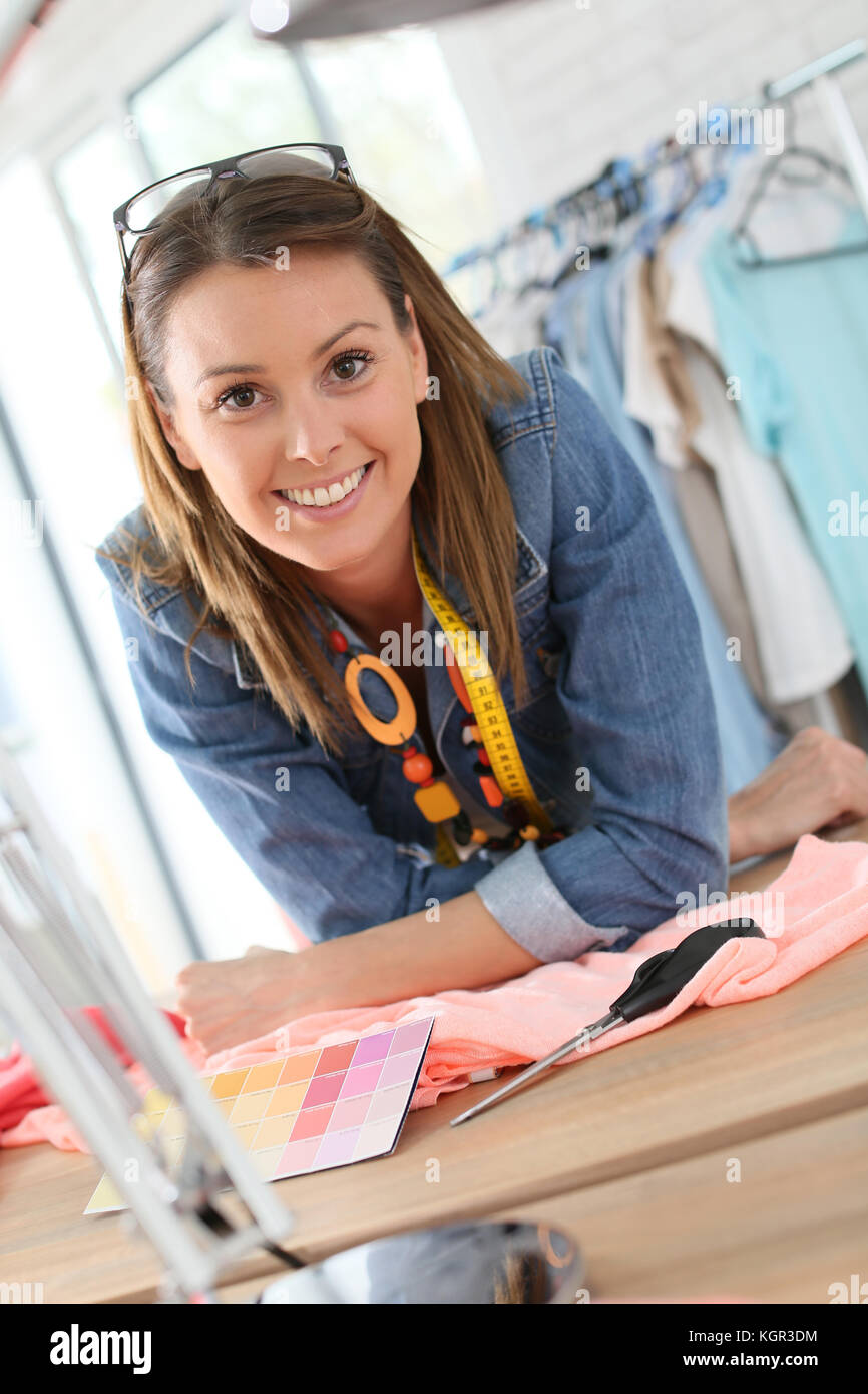 Portrait of cheerful dressmaker in designing studio - Stock Image