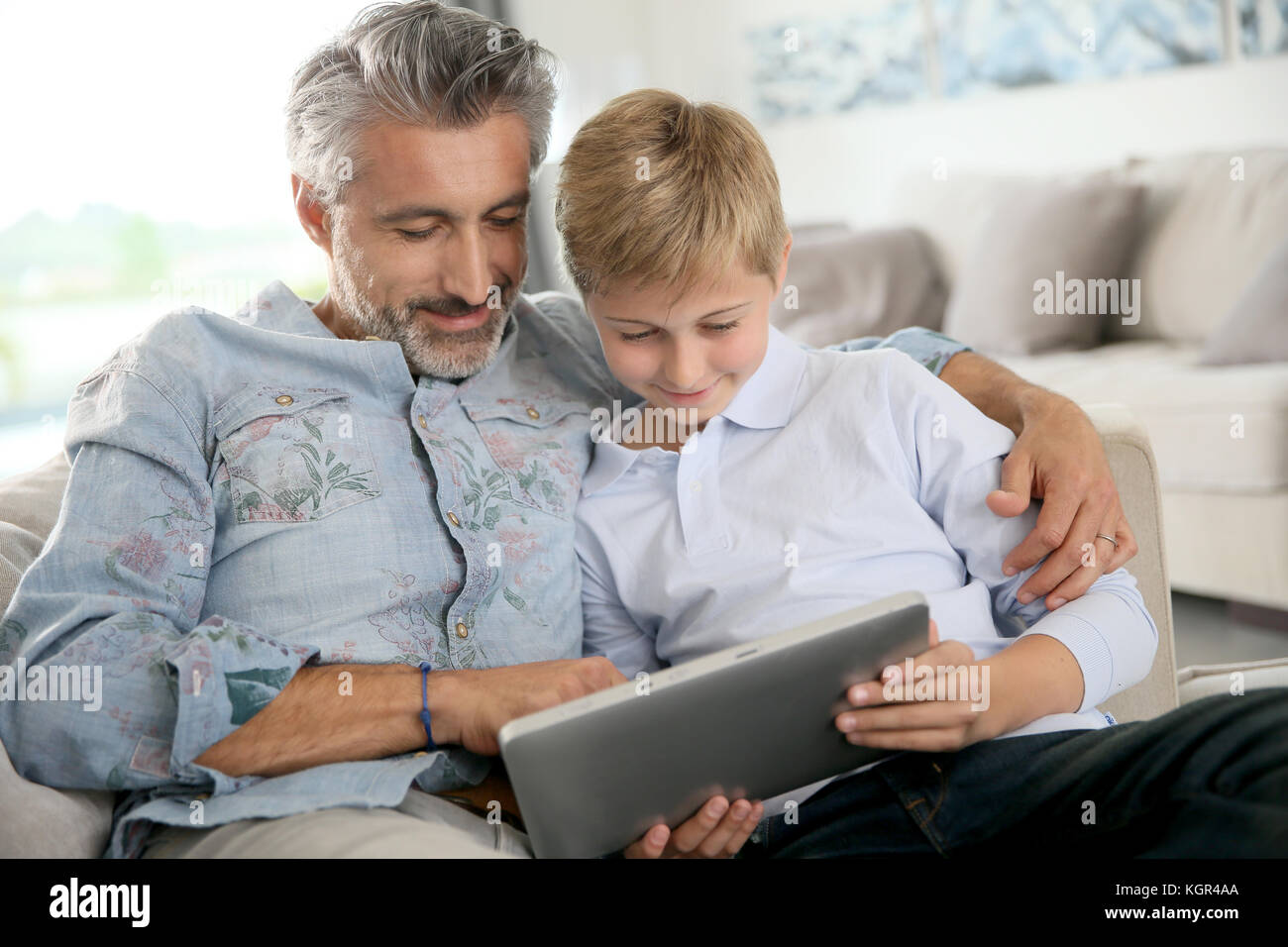 Father and son using digital tablet at home - Stock Image