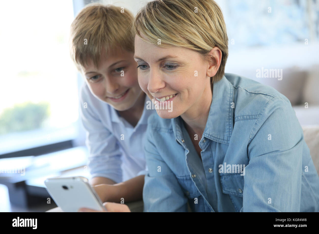 Mother and pre-teen using smartphone at home - Stock Image