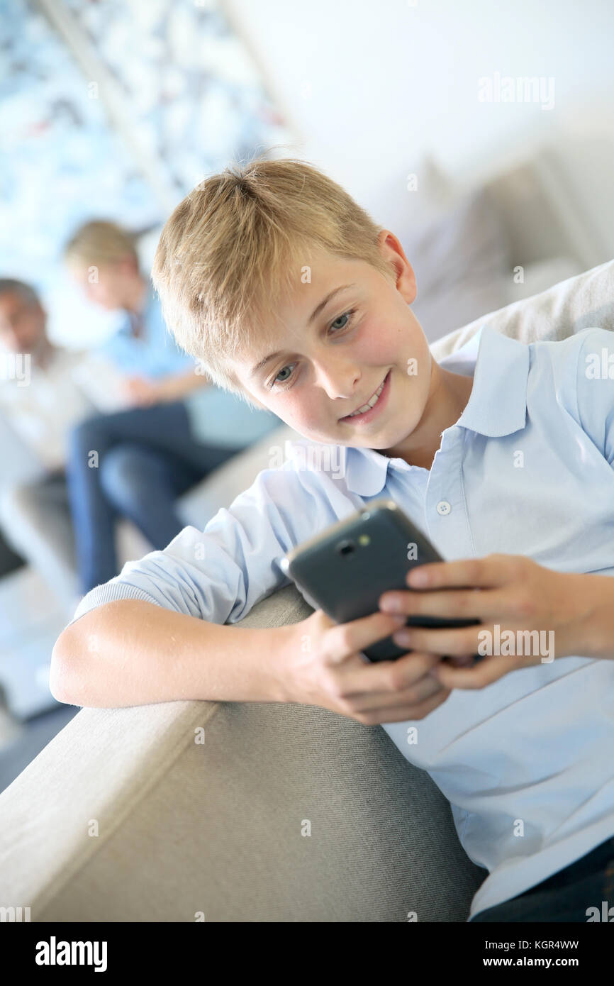 Pre-adolescent playing with smartphone, parents in background - Stock Image