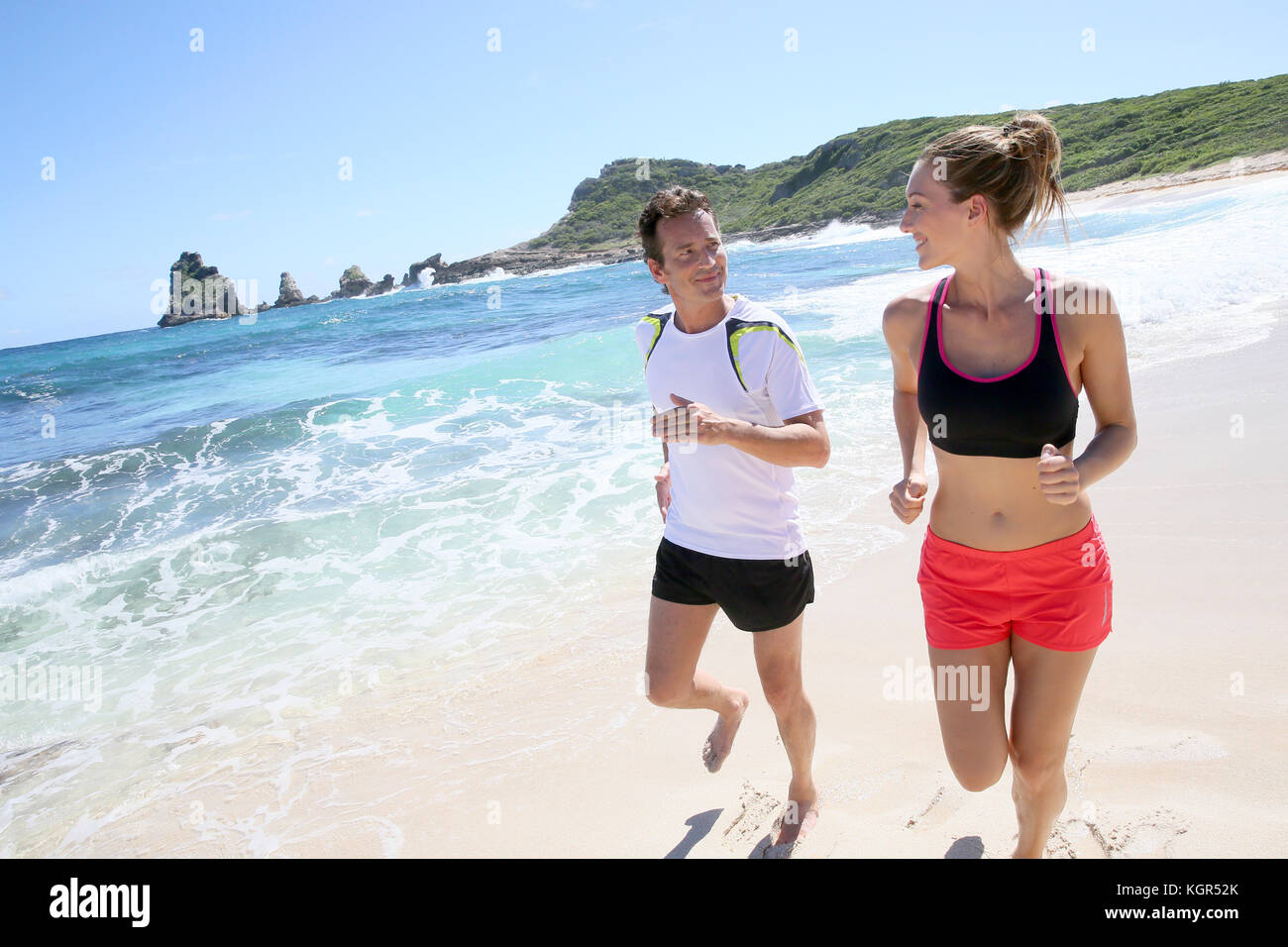 Couple runners exercising on a sandy beach - Stock Image