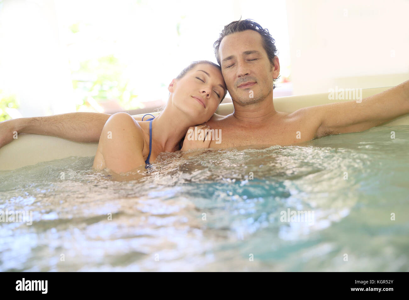 Romantic couple relaxing with eyes shut in jacuzzi - Stock Image
