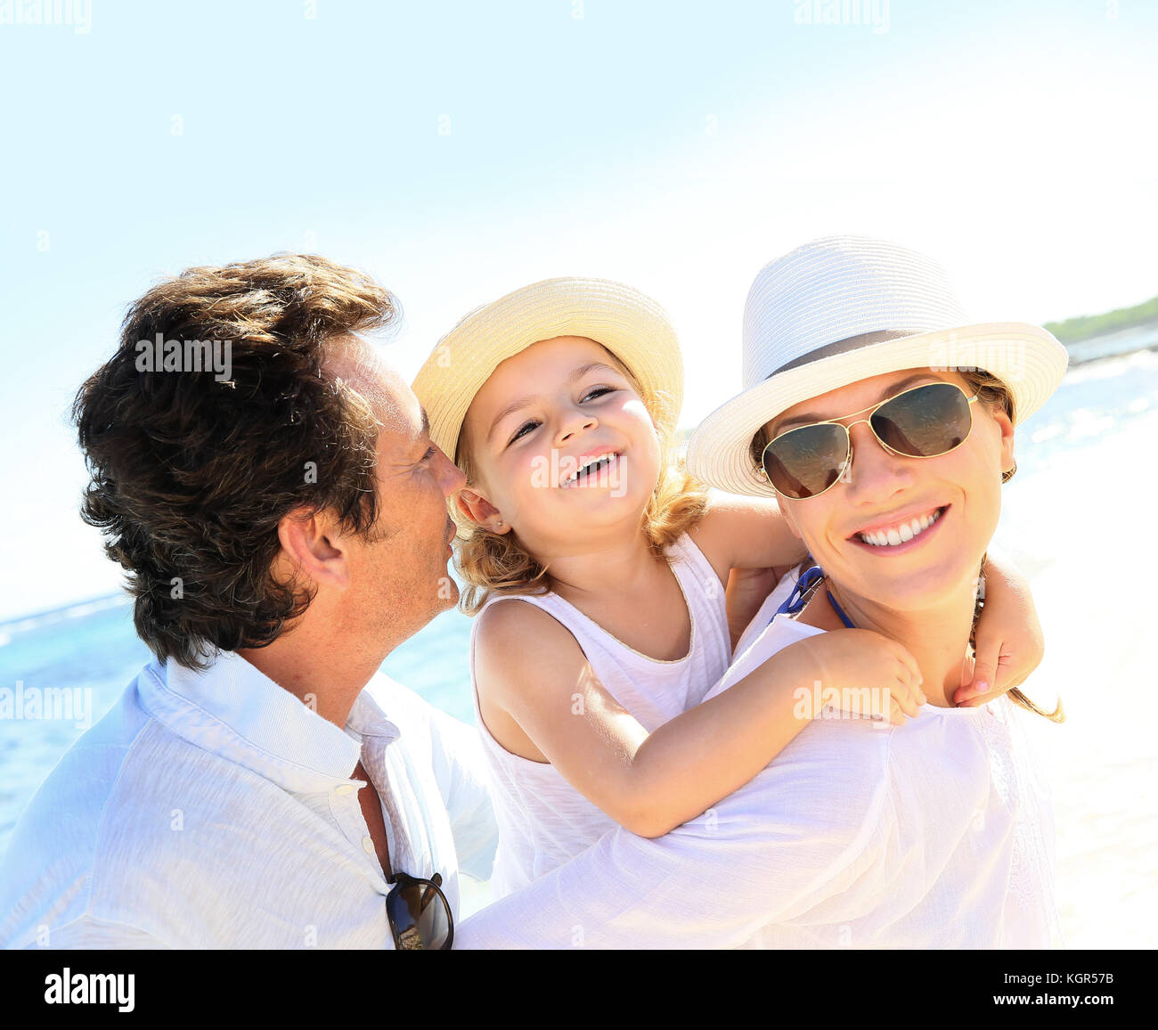 Portrait of happy family at the beach - Stock Image