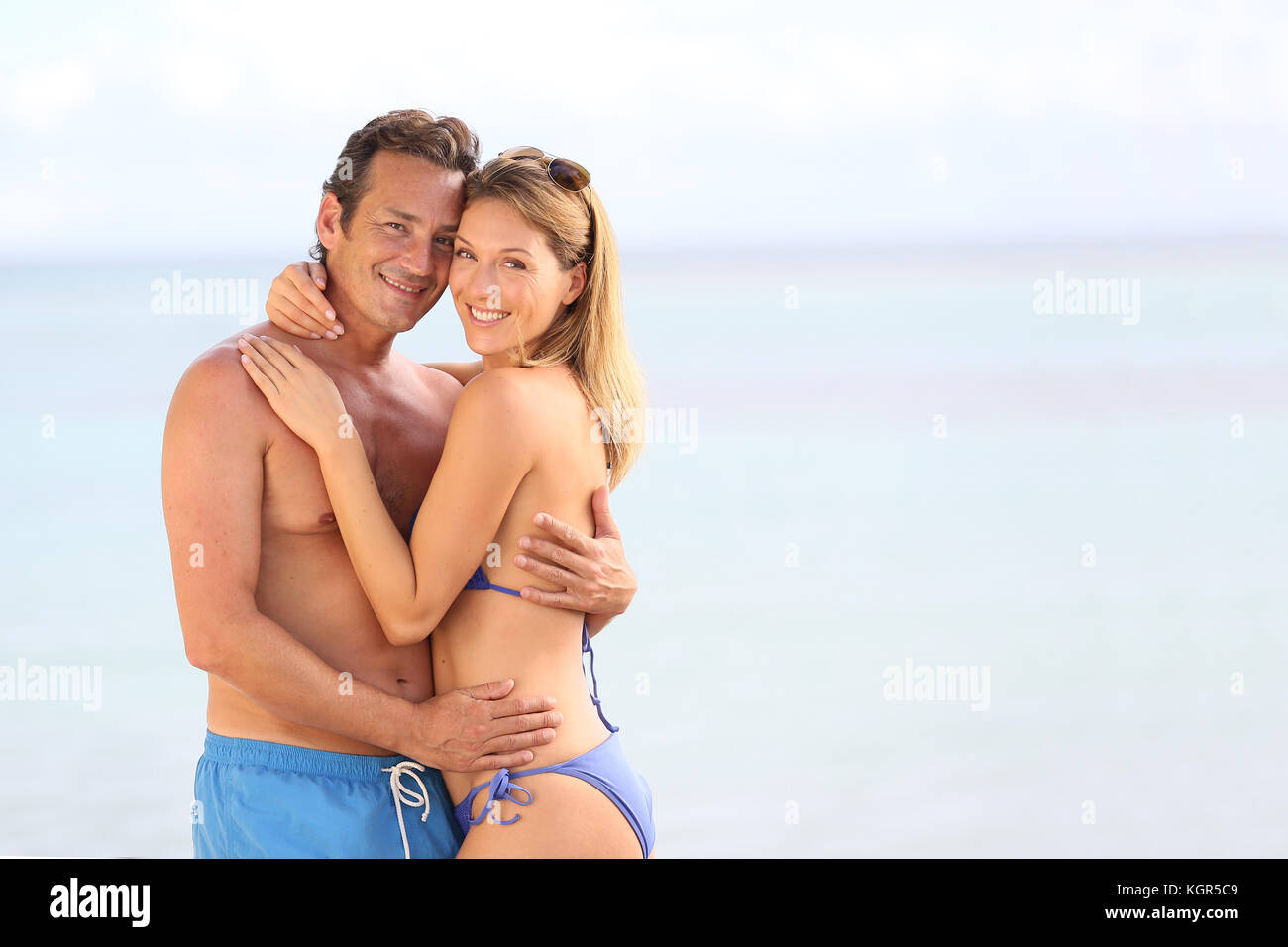 Loving couple in swimsuit embracing at the beach - Stock Image