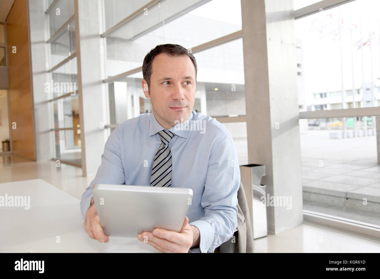 Businessman sitting in the office with electronic tablet - Stock Image