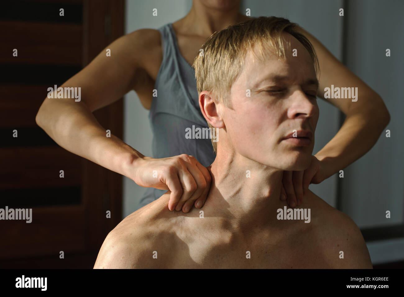 A woman makes a man a massage. She massages her shoulders - Stock Image