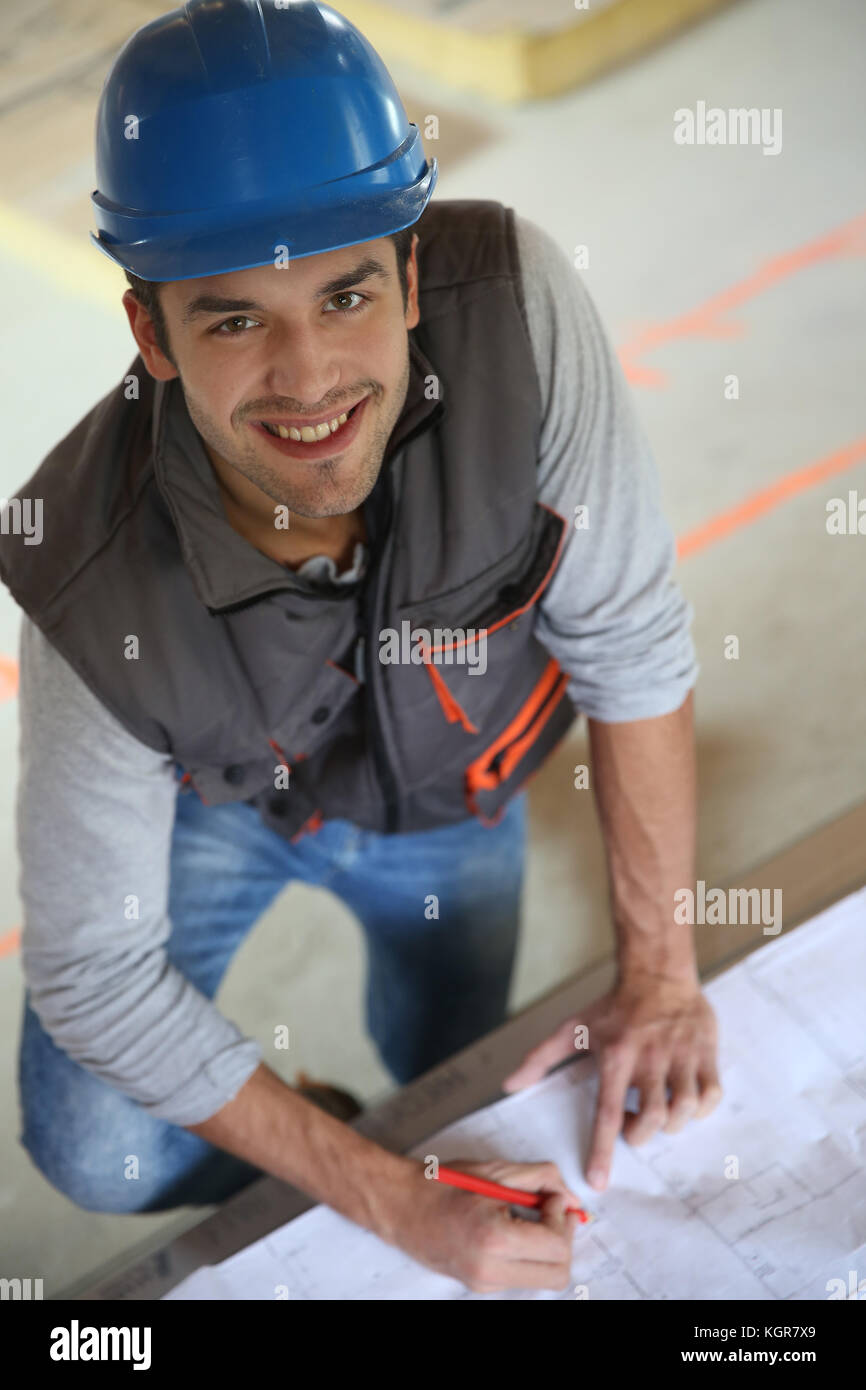 Construction worker checking blueprint - Stock Image