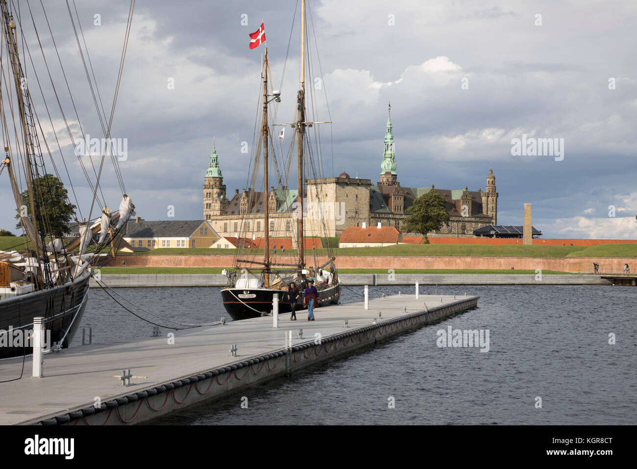Tall ship in harbour with Kronborg Castle used as setting for Shakespeare's Hamlet in distance, Helsingor, Zealand, - Stock Image
