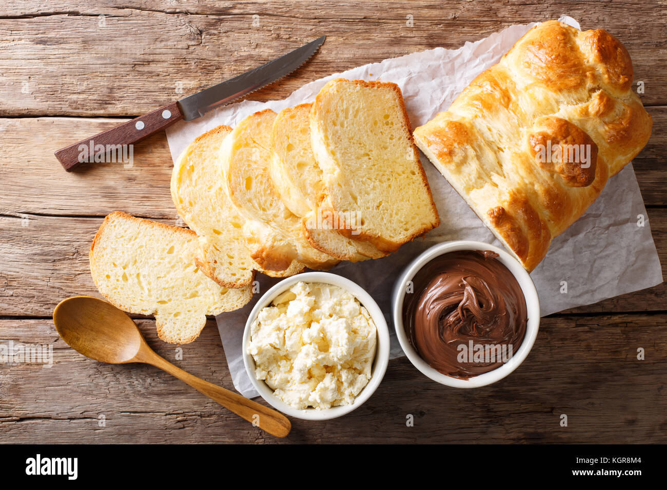 Freshly brioche bread and cream cheese, chocolate cream on the table. horizontal top view from above - Stock Image