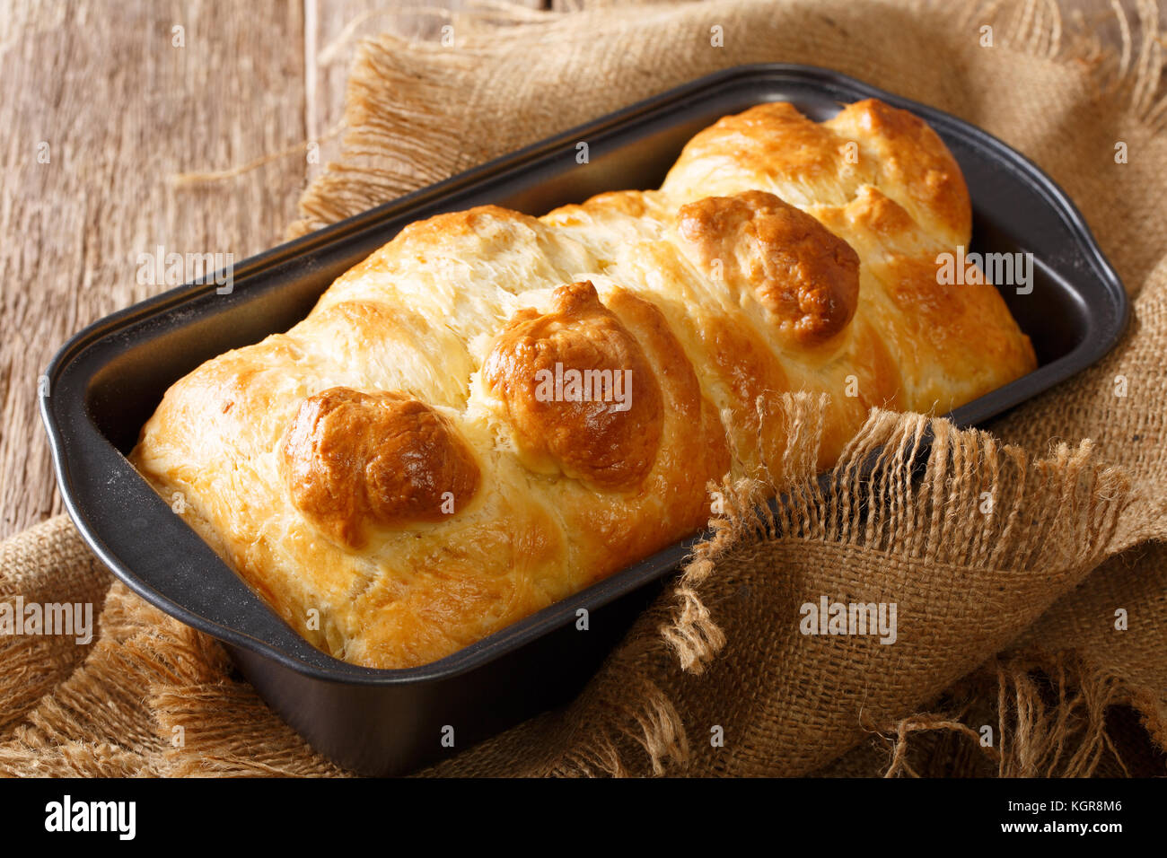 Hot aromatic brioche bread in a baking dish close-up on a table. horizontal - Stock Image