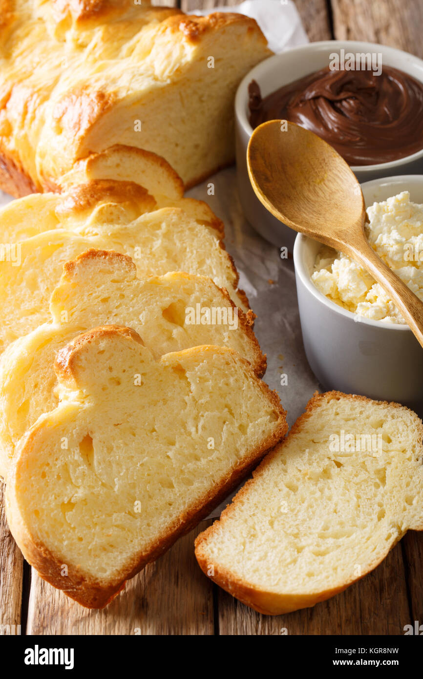 Freshly brioche bread and cream cheese, chocolate cream macro on the table. vertical - Stock Image