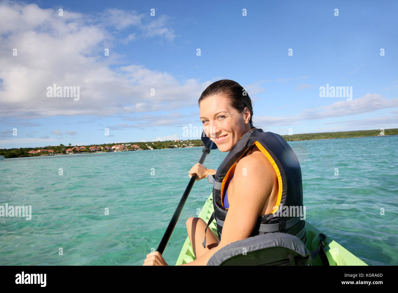 Woman paddling in canoe on blue lagoon - Stock Image