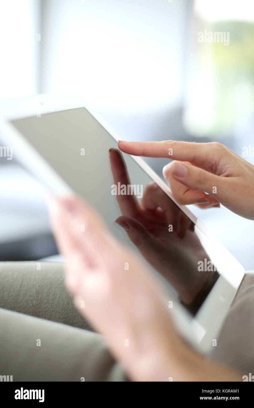 Closeup of hand sliding on digital tablet - Stock Image