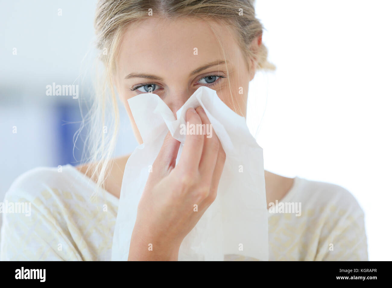 Young woman with cold blowing her runny nose - Stock Image