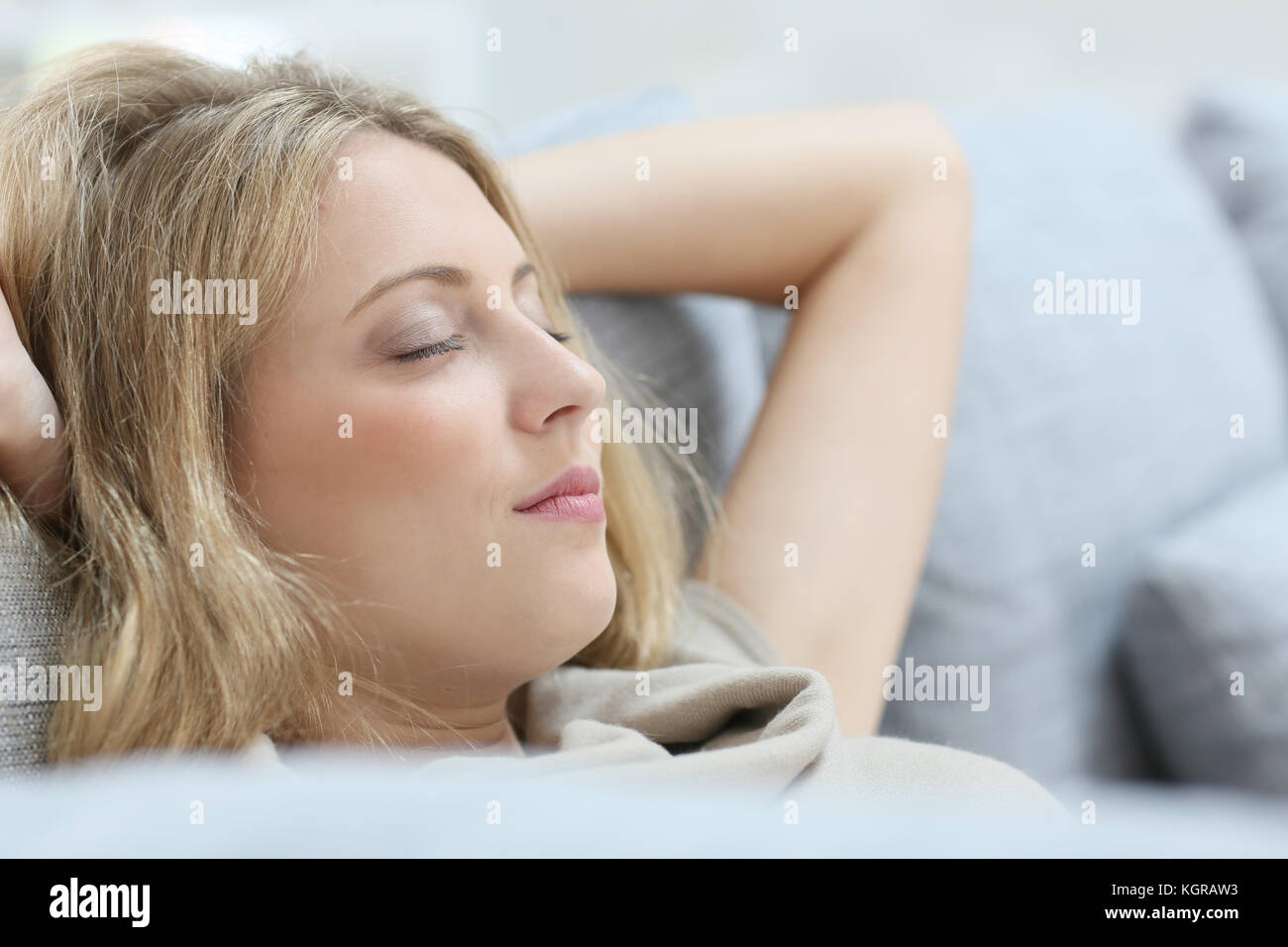 Blond woman in sofa relaxing with eyes shut - Stock Image