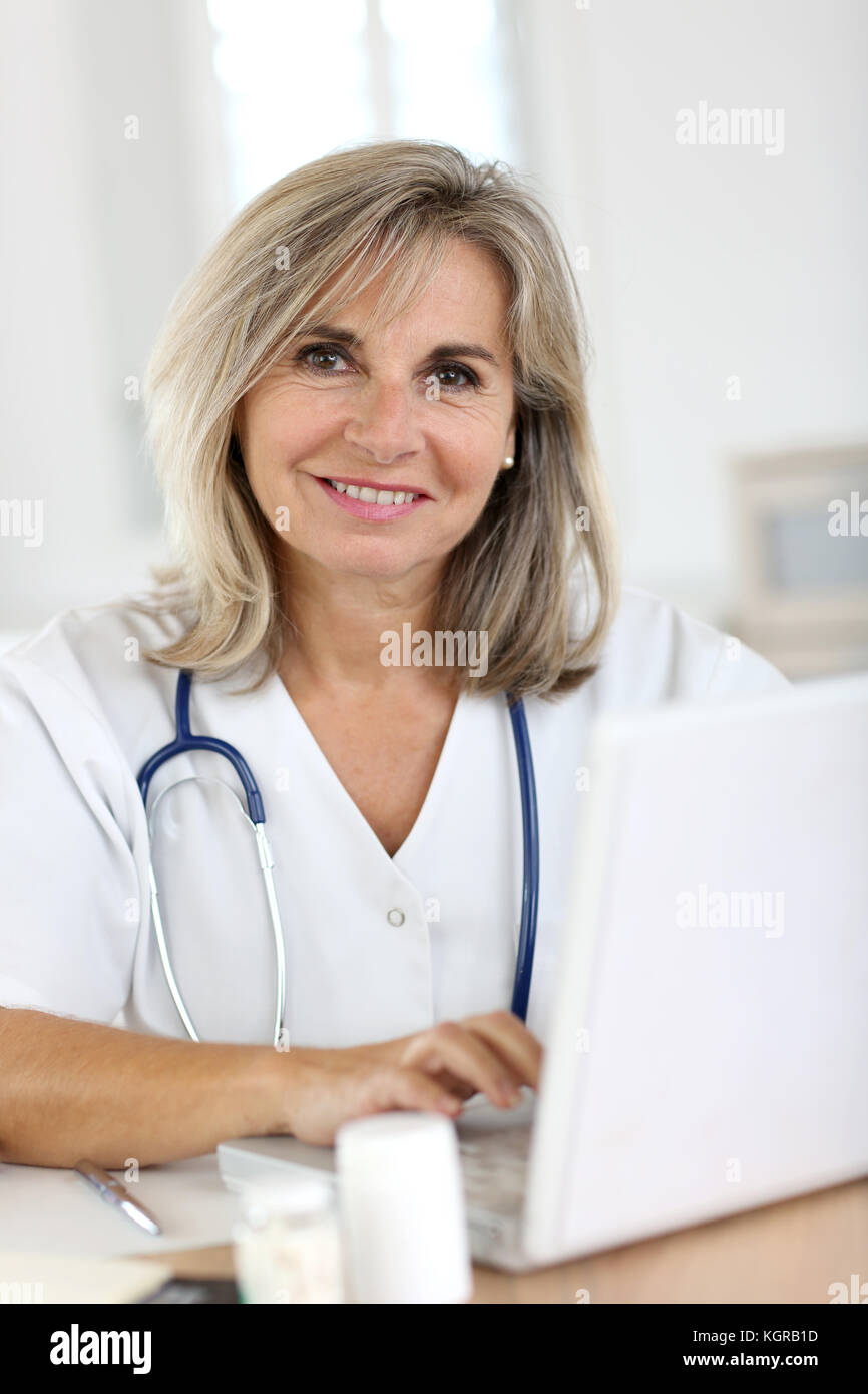 Portrait of smiling senior nurse in hospital - Stock Image