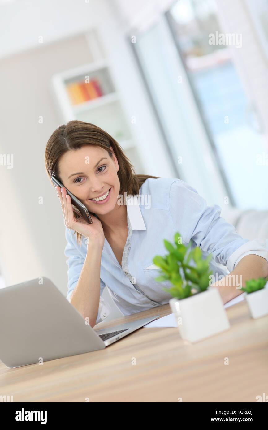 Woman in office talking on mobile phone - Stock Image