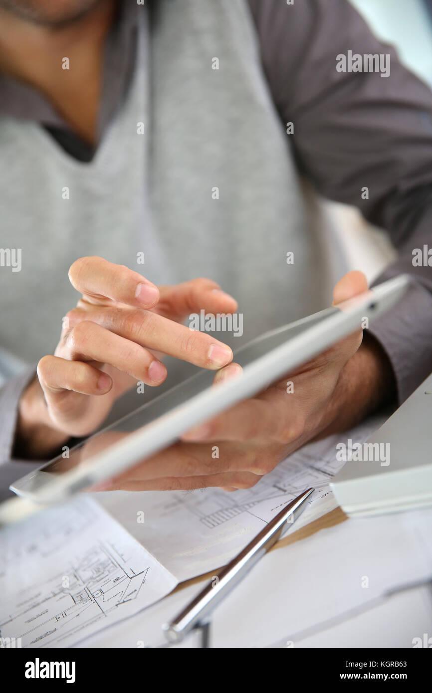 Closeup of man's hand using digital tablet - Stock Image