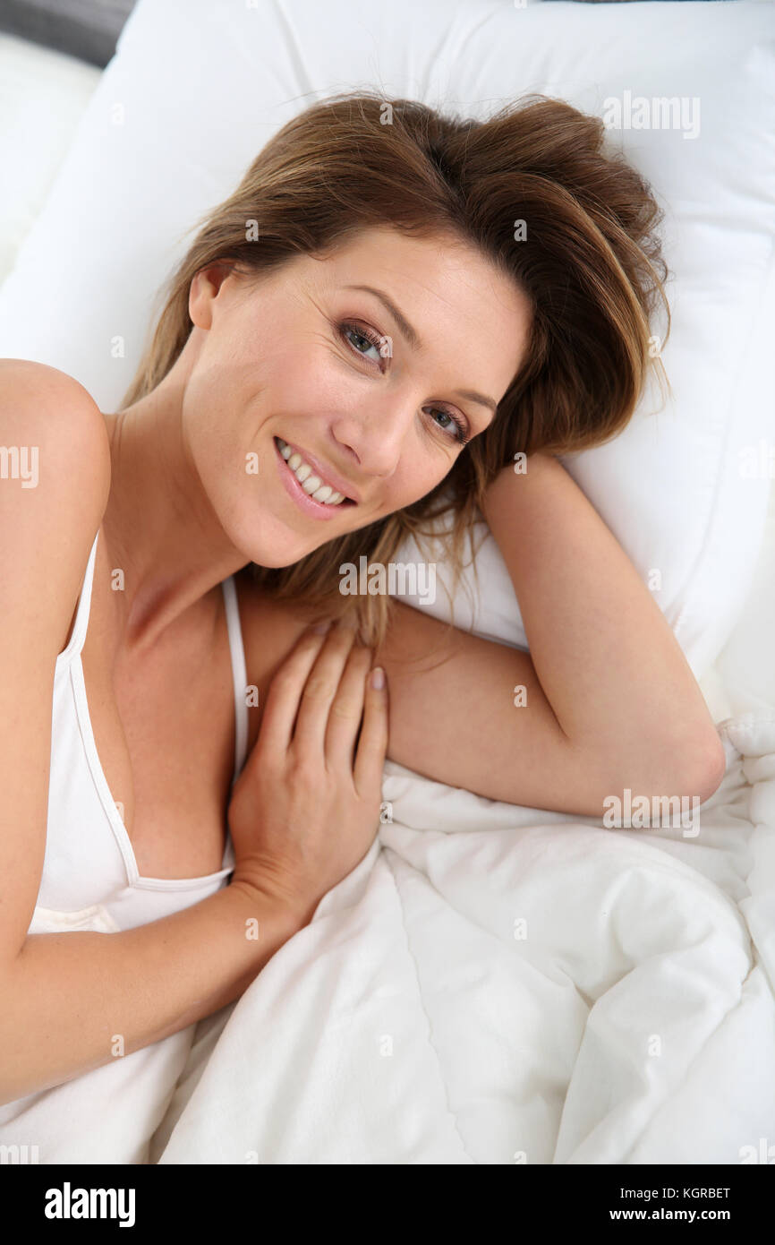Charming woman in bed looking at camera - Stock Image