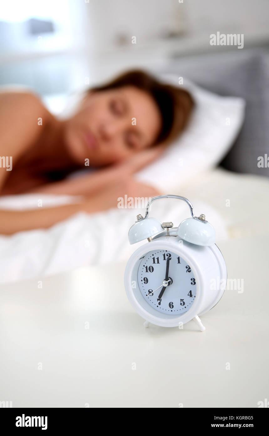Closeup of alarm clock set on bedroom table - Stock Image