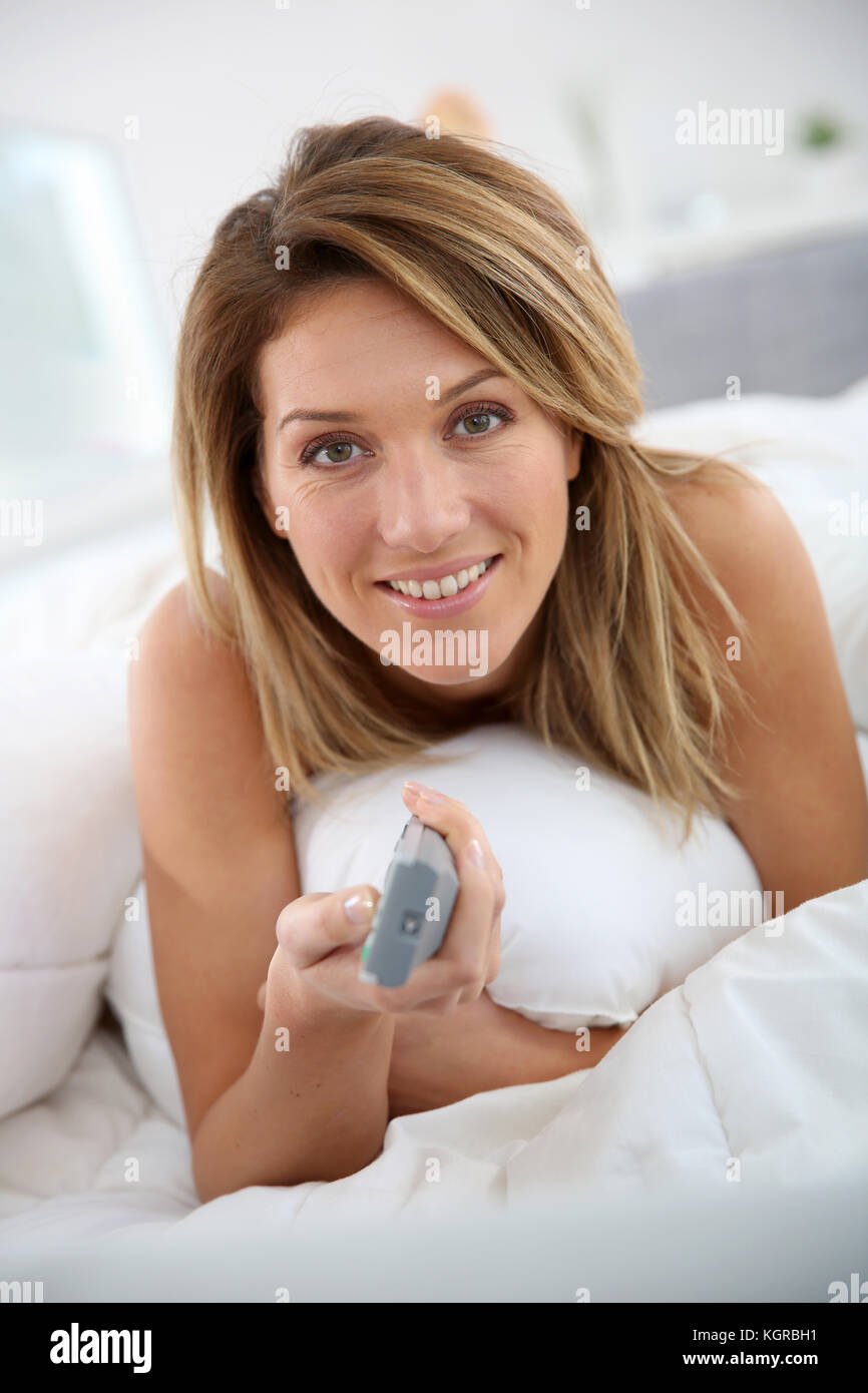 Woman laying in bed and watching television - Stock Image