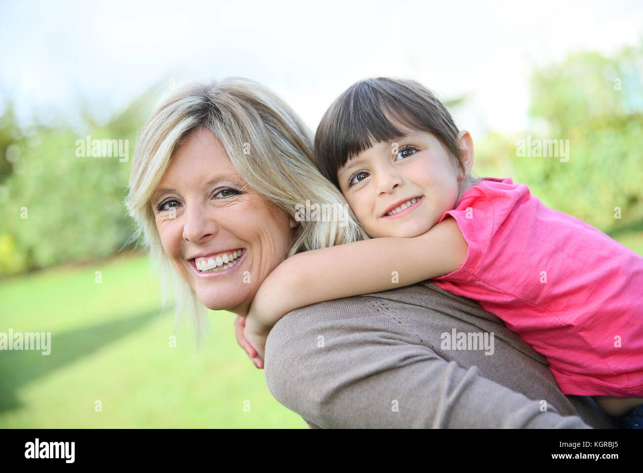 Mother giving piggyback ride to little girl - Stock Image
