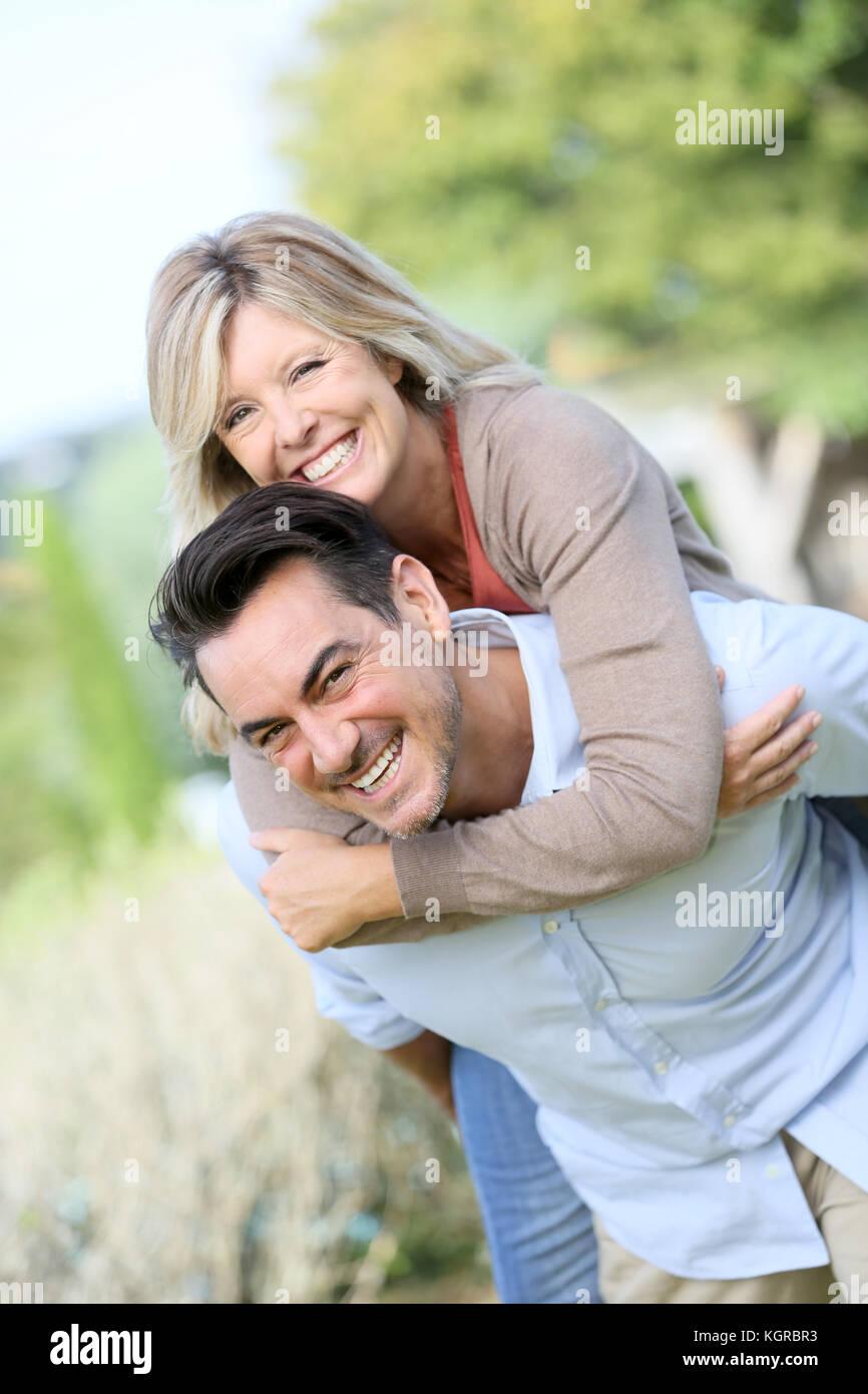Cheerful mature man giving piggyback ride to woman Stock Photo