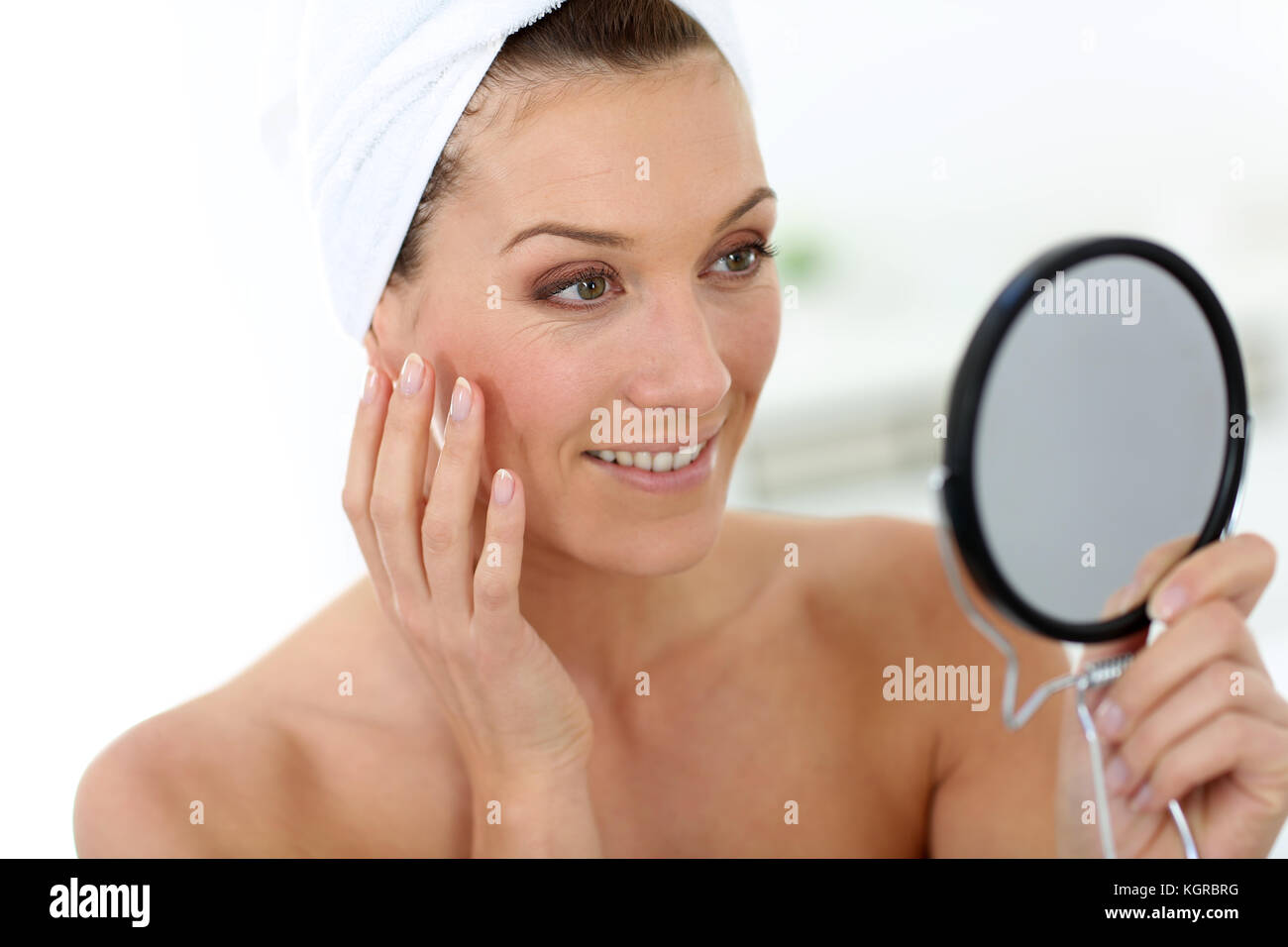 Middle-aged woman in bathroom looking at mirror - Stock Image