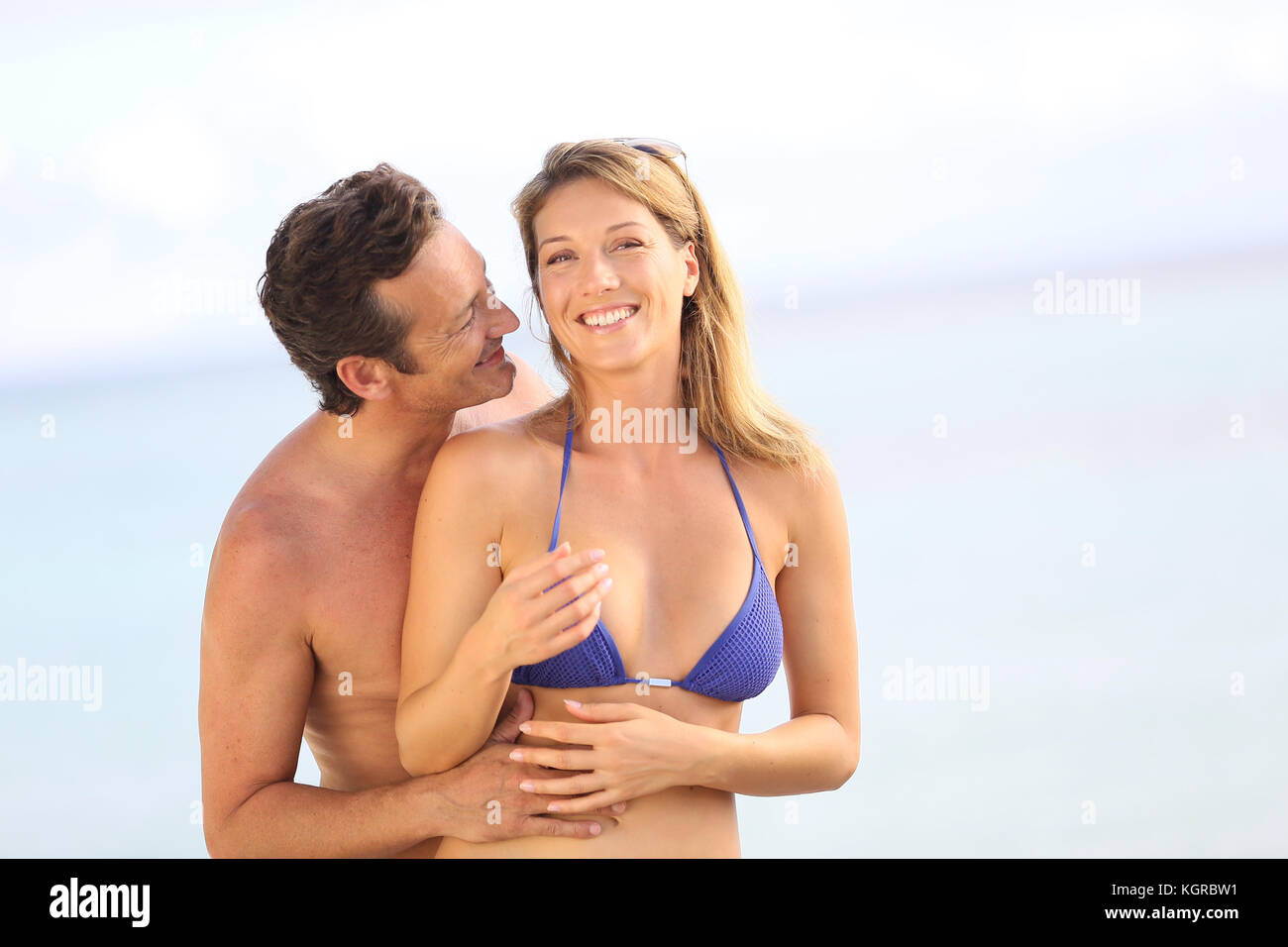 Cheerful 40-year-old couple at the beach - Stock Image