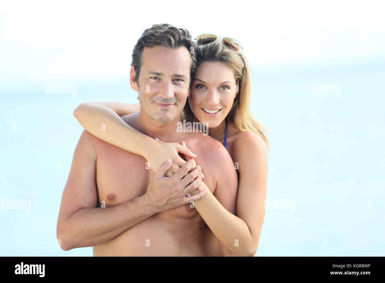 Portrait of middle-aged couple embracing by the beach - Stock Image