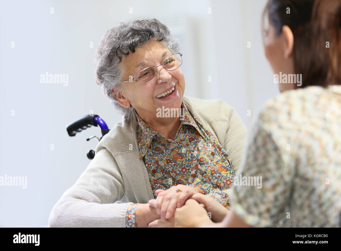 Elderly woman sharing good time with home carer - Stock Image