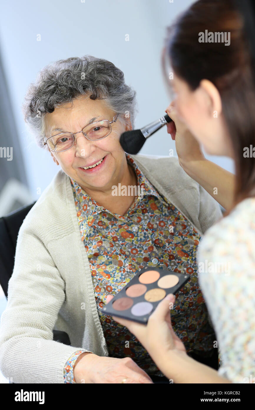 Home carer helping elderly woman to put makeup on - Stock Image