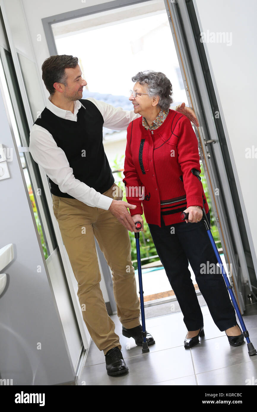 Man helping elderly woman with crutches - Stock Image