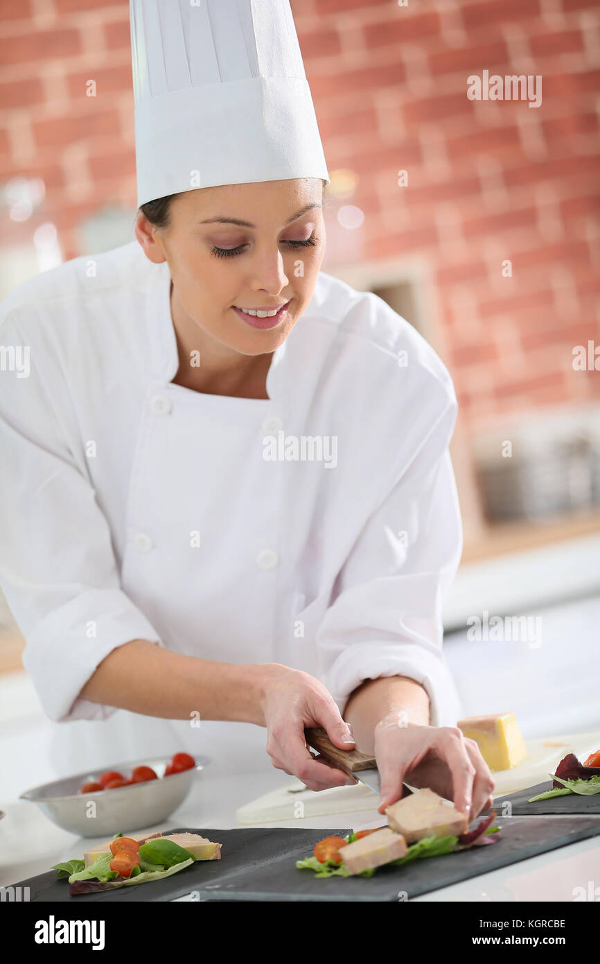 Young chef preparing plate of foie gras - Stock Image